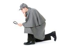 Sherlock: Detetive Using Magnifying Glass para examinar algo imagens de stock royalty free