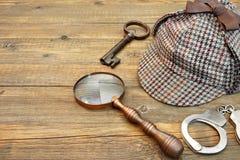 Sherlock Holmes Cap som är berömd som Deerstalker, tangent, handbojor och mor Arkivfoton
