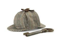 Sherlock Holmes Deerstalker Cap And Old-Weinlese-großer Schlüssel lokalisiert Lizenzfreie Stockbilder