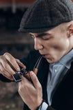 Sherlock holmes look, man in retro outfit, smoking, lighting woo Stock Photo