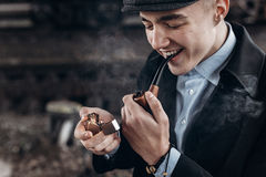 Sherlock holmes look, man in retro outfit, smoking, lighting woo Stock Image
