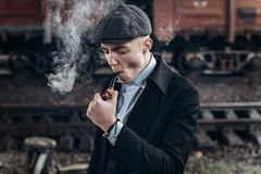 Sherlock holmes look, man in retro outfit, smoking wooden pipe. Stock Photos