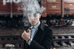 Sherlock holmes look, man in retro outfit, smoking wooden pipe. Royalty Free Stock Images