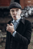 Sherlock holmes look, man in retro outfit, smoking wooden pipe. Royalty Free Stock Photos