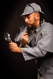 Sherlock Holmes with pipe and magnifying glass Royalty Free Stock Image