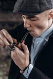 Sherlock holmes ser, mannen i den retro dräkten, att röka som tänder uppvaktar Arkivfoto