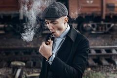 Sherlock holmes ser, mannen i den retro dräkten som röker träröret Arkivfoton