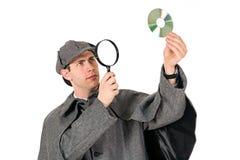 Sherlock: O homem examina o CD com lupa fotos de stock