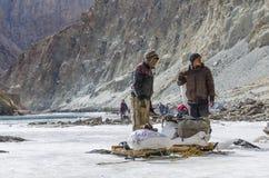 Sherpa bärande påfyllning på den djupfrysta floden Royaltyfri Foto