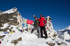 Sherpa and climber on summit. Sherpa and climber on the summit of Gokyo Ri on the Gokyo Trek with prayer flags in the background Royalty Free Stock Photo