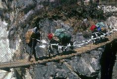 Sherpa en jakken die hangbrug kruisen Stock Foto's