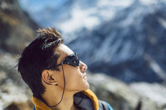 Sherpa Mountaineer looking at the summit. Profile portrait of young Sherpa wearing protective sunglasses in Himalayas Stock Photos