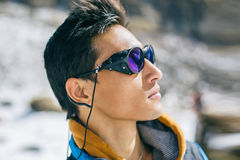 Sherpa mountaineer. Profile portrait of young Sherpa wearing protective sunglasses in Himalayas Stock Photo