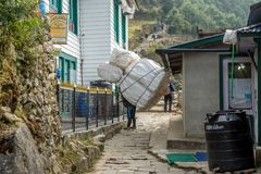 sherpa porters carrying heavy sacks in the Himalayas at Everest royalty free stock photos