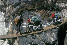 Sherpa and yak crossing suspension bridge Stock Photos