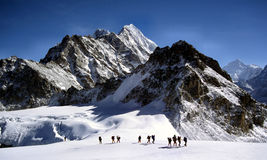 Sherpas crossing an Himalayam glacier. This is a photo of climbers and sherpas making a glacier traverse on the way to Mera Peak. In the far distance you can see Stock Images