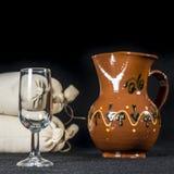 Sherry glass beside a pottery jug to serve wine Stock Image