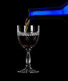 Sherry or port being poured into glass. Sherry, port or whisky being poured from blue wine bottle into an elegant cut glass and isolated against black Royalty Free Stock Photography