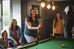 Shes`s Good at Pool. Small group of female friends playing a game of pool in a games room in a house royalty free stock image