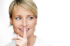 Shh. Young blond woman with her finger over her mouth Stock Image