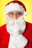 Shh...Aged Santa gesturing silence Stock Photos