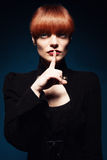 Shh finger. Beautiful woman with straight red hair doing shh with her finger Stock Photo