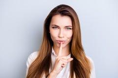 Shh! Houd mijn geheim Het aantrekkelijke flirty meisje in het witte kapsel van overhemdswithnice toont iemand om op lichtblauwe b royalty-vrije stock afbeelding