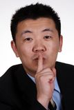 Shh! Keep Quiet. An asian businessman showing keep quiet sign royalty free stock image
