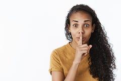 Shh não deslize a palavra O retrato da mulher afro-americano bonito entusiasmado excitada e feliz com exibição do cabelo encaraco fotografia de stock royalty free