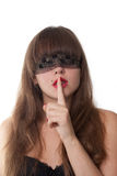 Shh. secret. Beautiful young girl with her finger over her mouth and  blindfold, over white background Stock Photography