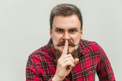 Shh sign. Anger businessman with beard and handlebar mustache. Looking at camera with silent sign. studio shot, on gray background royalty free stock photography