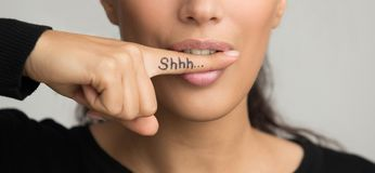 Shh, women`s secrets. Shhh written on the finger. Woman Bite Finfer with Shhh, Female Secrets concept royalty free stock photos