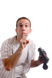 Shhh. A young man is telling the viewer to be quiet while he holds his set of binoculars, isolated against a white background Royalty Free Stock Images