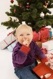 Shhh - chéri mignonne ouvrant sneakily des cadeaux de Noël Photographie stock libre de droits