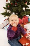 Shhh - Cute baby sneakily opening christmas gifts Royalty Free Stock Photography