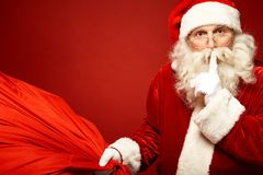 Shhh. Portrait of Santa Claus with huge red sack keeping forefinger by his mouth and looking at camera Royalty Free Stock Images
