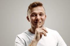 Shhhh? Halten Sie Ruhe Hübscher junger Mann im weißen Hemd, das Kamera betrachtet und Finger auf Lippen hält stockfotografie