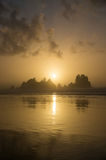 Shi Shi Beach Sunset Olympic National Park. In NW Washington State.  Sun sets as bands of cumulus clouds float by.  Ocean waves pulsing with the headlands in Stock Photo