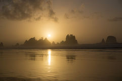 Shi Shi Beach Sunset Olympic National Park. In NW Washington State.  Sun sets as bands of cumulus clouds float by.  Ocean waves pulsing with the headlands in Stock Photography