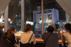 Shibuya, Tokyo, Japan - April 30, 2018: People sitting in coffee shop, watching Shibuya crosswalk in Tokyo, Japan. Shibuya Crossing is one of the busiest stock photo