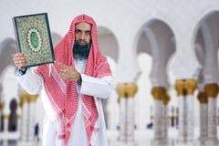 Shiekh árabe islámico que presenta Quran Imagen de archivo