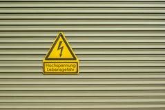 Shield Attention High voltage Danger to life on metal door with crosswise metal lamellas. Schild Achtung Hochspannung Lebensgefahr auf Metalltür mit Stock Photography