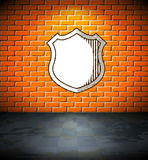 Shield on the brick wall Stock Photos