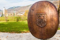 Shield with the Coat of arms of Mondsee, Austria. Metal shield with the Coat of arms of Mondsee in Seepromenade Lake promenade Park, St Michael Basilica on the Royalty Free Stock Photography