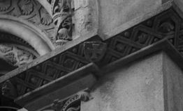 Shield with cross on the church main entrance. Shot in black and white detail of the sculpture on the facade of this historic building representing some royalty free stock photography