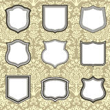 Shield Frames on Damask Background. Set of shield frames on seamless damask background.  Damask background is behind a clipping mask.  Colors are global, and Stock Image