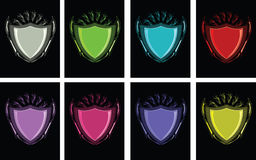 Shield vectors in several colors. Blank shiny shield in eight colors on black backgrounds Stock Image