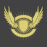 Shield with wings. Gold wings and shield on gray background Royalty Free Stock Photography
