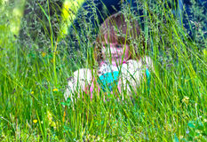 Shielded by grass. Two year old girl almost age three sitting in a field or grassy area Stock Photos