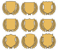 Shields with laurel wreaths. Set of different shaped golden shields with laurel wreaths and copy space, isolated on white background vector illustration